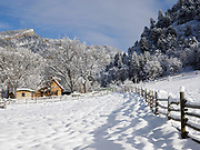 View of snow-covered fields, cabin and canyon.