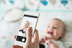 Mother photographing her baby with mobile phone