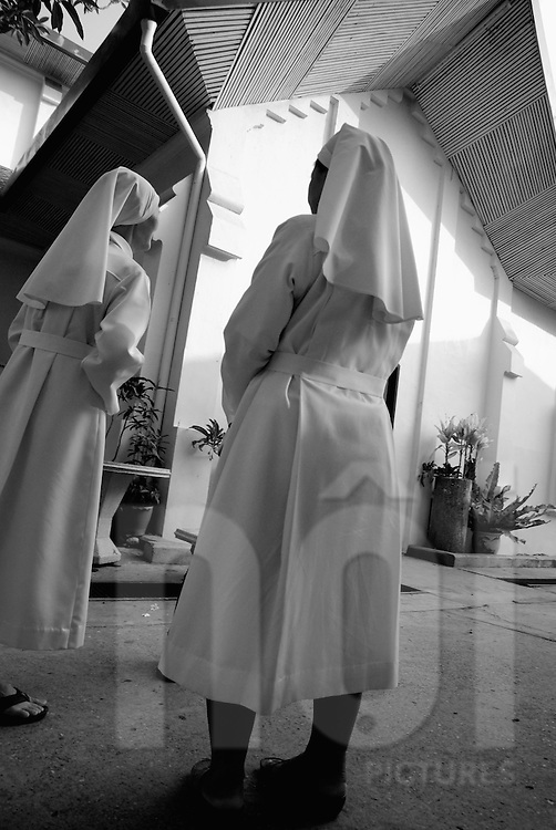 Two laos nuns are standing in front of a church in Vientiane, Laos, Asia