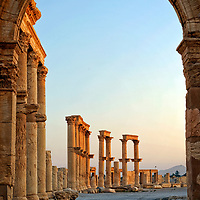 Palmyra. Syria. An Arch opening in the south portico of the Great Colonnade street gives access to a road that runs around the hemicycle of the theatre. Constructed in the 2nd century AD, the whole Great Colonnade street cuts through the ancient city from east to west and is more than one kilometre in length. Half-way up each column are brackets that held projecting statues over the roadway.