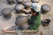Lao woman molds clay pots in Vientiane Asia