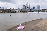 A young woman models a pink flowing dress on the Bankside foreshore of the river Thames, opposite the City of London, the capital's financial district, on 1st September 2021, in London, England.