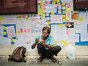"""06 JULY 2015 - BANGKOK, THAILAND:  A man carves wooden toys under a wall covered in """"Post It"""" notes related to the arrest of 14 students for violating orders related to political assembly. More than 100 people gathered at Thammasat University in Bangkok Monday to show support for 14 students arrested two weeks ago. The students were arrested for violating orders against political assembly. They face criminal trial in military courts. The students' supporters are putting up """"Post It"""" notes around Bangkok and college campuses up country calling for the students' release.     PHOTO BY JACK KURTZ"""
