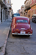 A classic old red Peugeot car parked on a street corner. probably from the 1950s 50s, perhaps a 203 Montevideo, Uruguay, South America