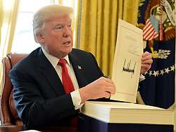United States President Donald J. Trump points to the press during an event to sign the $1.5 trillion tax cut bill in the Oval Office of the White House, December 22, 2017, in Washington, DC, prior to his departure to Mar-a-Lago, Florida for the holidays. Credit: Mike Theiler / Pool via CNP. 22 Dec 2017 Pictured: United States President Donald J. Trump displays his signature after signing the $1.5 trillion tax cut bill, stacked on his desk, in the Oval Office of the White House, December 22, 2017, in Washington, DC, prior to his departure to Mar-a-Lago, Florida for the holidays. Credit: Mike Theiler / Pool via CNP. Photo credit: Mike Theiler - Pool via CNP / MEGA TheMegaAgency.com +1 888 505 6342