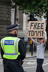 London, UK. 9th June, 2018. A young supporter of Tommy Robinson, former leader of the far-right English Defence League, displays a 'Free Tommy' sign to anti-fascists protesting against the March for Tommy Robinson outside Downing Street.