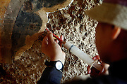 A Japanese woman belonging to the maintenance and restoration team in Bamiyan is working on emergency fixtures on the walls of an ancient Buddhist cave on the premises of the archaeological site. The Japanese team of experts has been visiting the town for various years to find a long-term solution to its slow but unceasing disappearance. The Buddhas of Bamiyan were two 6th century monumental statues of standing Buddhas carved into the side of a cliff in the Bamiyan valley in the Hazarajat region of central Afghanistan, situated 230 km northwest of Kabul at an altitude of 2500 meters. The statues represented the classic blended style of Gandhara art. The main bodies were hewn directly from the sandstone cliffs, but details were modelled in mud mixed with straw, coated with stucco. Amid widespread international condemnation, the smaller statues (55 and 39 meters respectively) were intentionally dynamited and destroyed in 2001 by the Taliban because they believed them to be un-Islamic idols. Once a stopping point along the Silk Road between China and the Middle East, researchers think Bamiyan was the site of monasteries housing as many as 5,000 monks during its peak as a Buddhist centre in the 6th and 7th centuries. It is now a UNESCO Heritage Site since 2003. Archaeologists from various countries across the world have been engaged in preservation, general maintenance around the site and renovation. Professor Tarzi, a notable An Afghan-born archaeologist from France, and a teacher in Strasbourg University, has been searching for a legendary 300m Sleeping Buddha statue in various sites between the original standing ones, as documented in the old account of a renowned Chinese scholar, Xuanzang, visiting the area in the 7th century. Professor Tarzi worked on projects to restore the other Bamiyan Buddhas in the late 1970s and has spent most of his career researching the existence of the missing giant Buddha in the valley.
