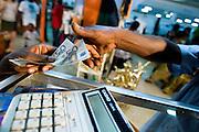 Money exchanges hands as a customers buys from a vendor at the 22nd Salon International de l'Artisanat de Ouagadougou (SIAO) in Ouagadougou, Burkina Faso on Saturday November 1, 2008.