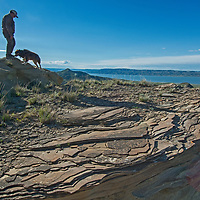A hker and his dog stand explore eroded rock features overlooking Fort Peck Reservoir in Charles M. Russell National Wildlife Reserve, Montana.