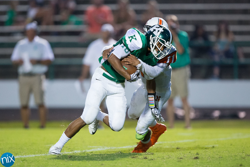 Shymere Scott (10) of the A.L. Brown Wonders fights for additional yards while being hit by IJ Sturdivant (11) of the Northwest Cabarrus Trojans at A.L. Brown High School on September 5, 2016 in Kannapolis, North Carolina.  The Wonders defeated the Trojans 48-0.  (Brian Westerholt/Special to the Tribune)