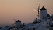 Classic beautiful sunset view of Oia windmills on Santorini, Greece.