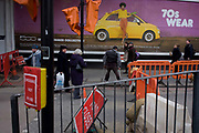 Pedestrians walk beneath a wide billboard advertising the Fiat 500 with a 70s fashion theme. A man on crutches awkwardly walks across the road and on to the far pavement beneath the image of the model and the yellow Fiat car. Roadworks are being carried out on this junction, part of the regeneration of the nearby London Bridge mainline rail station. The road is closed and the crossing not use on the south side of the Thames in the borough of Southwark.
