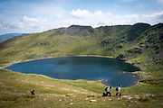 Walkes pass Red Tarn lake high up on the eastern flank of Helvellyn Mountain, English Lake District, Cumbria, United Kingdom on the 2nd of August 2021. Red Tarn is a glacial lake formed with the glacier that carved our the eastern side of the mountain melted. It is the habitat of the rare and endangered Schelly fish.