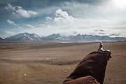 Near the Kyzyl Qorum camp, a Kyrgyz man points to the valley leading to Pakistan, a 6 days journey..Trekking with yak caravan through the Little Pamir where the Afghan Kyrgyz community live all year, on the borders of China, Tajikistan and Pakistan.