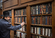 """A Jewish man picks a siddur from one of the wooden bookshelves that stand near the timeworn stones. Despite the large number, supply can to run low on crowded days. A siddur is a Jewish prayer book, containing a set order of daily prayers. The word """"siddur"""" comes from a Hebrew root meaning """"order""""."""