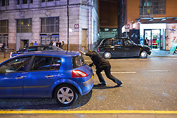 © Licensed to London News Pictures . Manchester , UK . 05/04/2015 . A man comes to the aid of the driver of a broken down car , which has been causing a road blockage on Withy Grove in Central Manchester . Revellers on a Saturday night out during the Easter Bank Holiday weekend . Photo credit : Joel Goodman/LNP