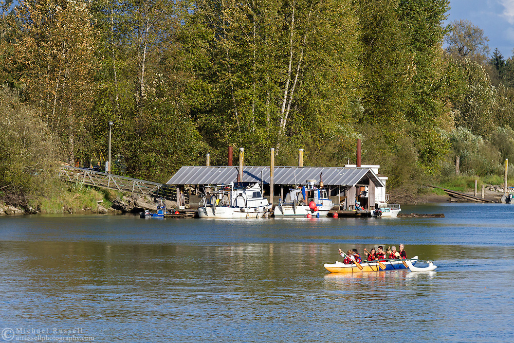 Boaters from the Fort Langley Rowing Club paddle past fishing boats in the Bedford Channel at Fort Langley, British Columbia, Canada