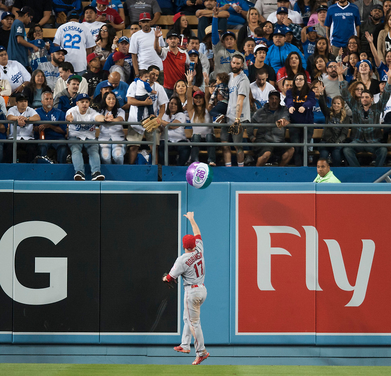 The Angels' Shane Robinson tosses a beach ball over the outfield wall Tuesday night at Dodger Stadium.<br /> <br /> / //ADDITIONAL INFO:   <br /> <br /> angels.0518.kjs  ---  Photo by KEVIN SULLIVAN / Orange County Register  -- 5/17/16<br /> <br /> The Los Angeles Angels take on the Los Angeles Dodgers in inter-league play at Dodger Stadium Tuesday night.