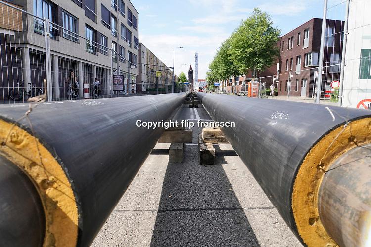 Nederland, Enschede, 22-7-2019 In de stad wordt stadsverwarming aangelegd. Lange buizen liggen klaar op straat om in de grond gebracht te worden. De warmte komt van de vuiverbranding, afvalverbranding, in Hengelo .Foto: Flip Franssen