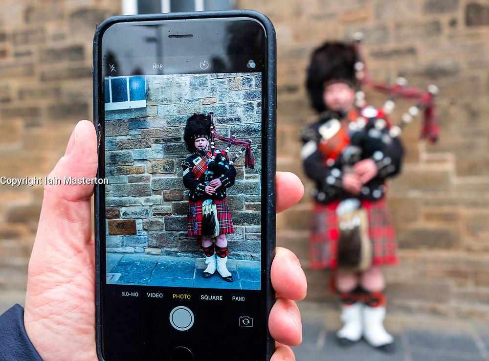Tourist taking photo of Scottish man in tartan playing bagpipes on the Royal Mile in Edinburgh Old Town, Scotland, United Kingdom