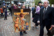 On a day when 400,000 public sector workers go on strike over cuts, pay and pensions, some protest art against NHS cuts depicting David Cameron and Nick Clegg hammering nails into a crucified Jesus figure. London, UK.