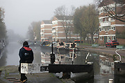 A work crew open a lock on Regents Canal on a misty morning on 27th of November 2020 in Hackney, London, United Kingdom. The crew is from the Canal and River Trust and are on their way further up the canal.