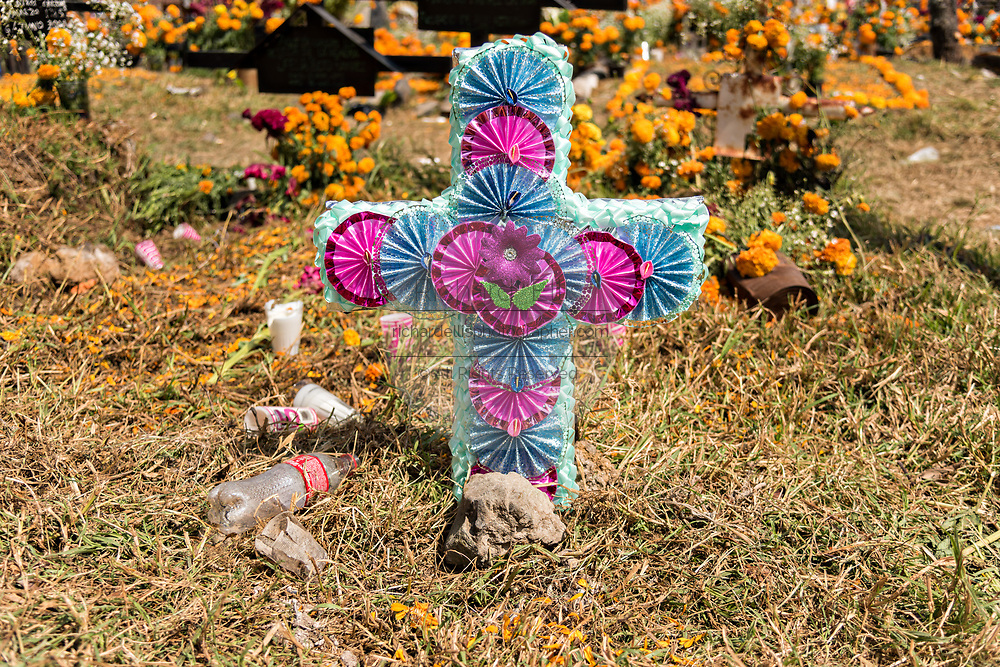 Litter next to the decorated grave marker during the Day of the Dead festival November 2, 2017 in Ihuatzio, Michoacan, Mexico.  The festival has been celebrated since the Aztec empire celebrates ancestors and deceased loved ones.