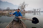Portrait of a young man paddling a boat on Dal Lake, Srinagar, Kashmir, India