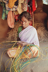 Indian girl affected by polio; member of selfhelp group supported by charity ADD India; weaving basket using coloured threads,