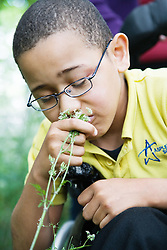 Boy with Cerebral Palsy sniffing a flower,