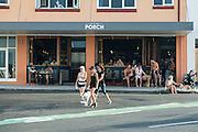 Dog walkers pass Porch cafe and restaurant, Bondi, Sydney, Australia.