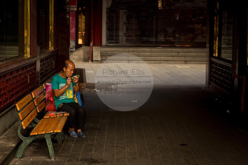 A homeless man shaves in the Yu Yuan bazaar in Shanghai, China