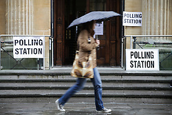 © Licensed to London News Pictures. 07/05/2015. Bristol, Avon, UK. A woman with an umbrella walking past the Corn Street polling station in Bristol for the 2015 UK General Election today, 7th May 2015. Photo credit : Rob Arnold/LNP