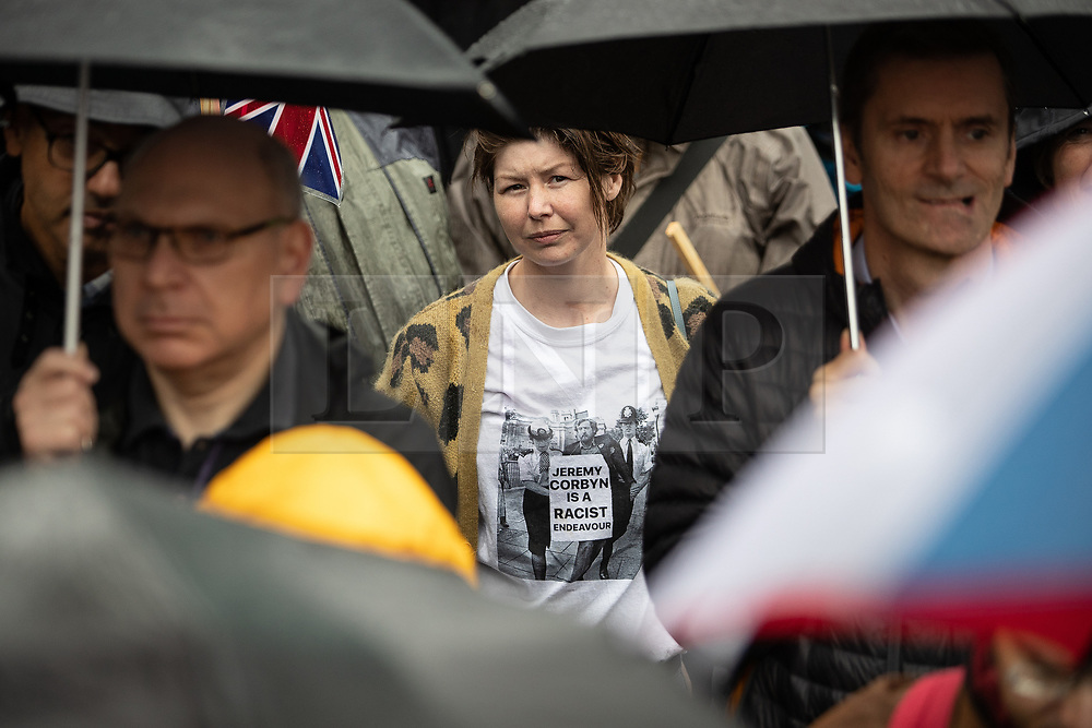 """© Licensed to London News Pictures . 16/09/2018. Manchester, UK. A woman wearing a t-shirt with a photograph of Jeremy Corbyn being detained by police from a historical anti-Apartheid rally , with the words """" Jeremy Corbyn is a racist endeavour """" . Thousands of people including the UK's Chief Rabbi and several Members of Parliament attend a demonstration against rising anti-Semitism in British politics and society , at Cathedral Gardens in Manchester City Centre . Photo credit : Joel Goodman/LNP"""