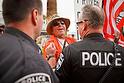 22 OCTOBER 2010 - PHOENIX, AZ:  BILL DEMSKI, from Glendale, AZ, and an opponent of the Tea Party, argues with police before a Tea Party rally Friday. The police asked Demski to leave the venua because the organizers had rented the space. About 300 people attended a Tea Party rally on the lawn of the Arizona State Capitol in Phoenix Friday. They demanded lower taxes, less government spending, repeal of the health care reform bill, and strengthening of the US side of the US - Mexican border. They listened to Arizona politicians and applauded wildly when former Alaska Governor Sarah Palin and her son, Trig, made a surprise appearance. The event was a part of the Tea Party Express bus tour that is crossing the United States.     Photo by Jack Kurtz