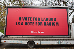London, UK. 26 November, 2019. A hoarding bearing the words 'A Vote for Labour is a Vote for Racism' parked outside the Bernie Grant Arts Centre in Tottenham before the arrival of Labour Party leader Jeremy Corbyn to launch Labour's new Race and Faith Manifesto.