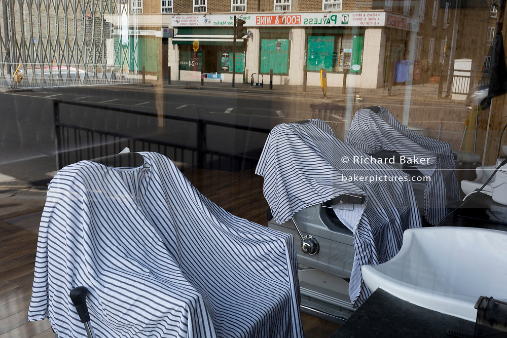 At the beginning of the second week of the UK's Coronavirus lockdown and in accordance with government guidelines for social distancing and the forced closure of all shops and local businesses, hairdressing gowns are draped over customer chairs in a closed mens' barber's business in East Dulwich, on 30th March 2020, in London.