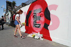 A woman lays flowers next to a mural of Savita Halappanavar in Dublin, as Ireland goes to the polls to vote in the referendum on the 8th Amendment of the Irish Constitution.