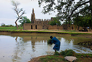 Man washing millet straw in a lake formed by rain in front of Kani-Kombolé village mosque. The Dogon Country is the most visited part of Mali with tourists visiting its tipical  villages that can be located on the cliff, on the sandy plain or in the rocky plateau