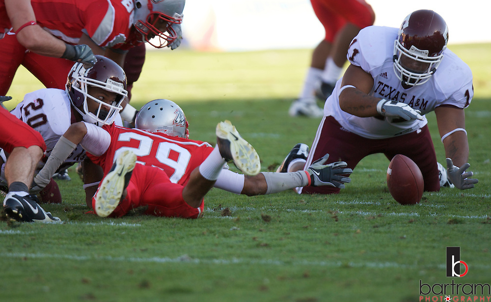 Texas A&M running back Jovorskie Lane, right, and New Mexico safety Blake Ligon reach for a fumble at the University of New Mexico on Saturday, Sept. 6, 2008 in Albuquerque, New Mexico.