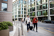 Business people chatting and walking through the streets of St Helier past the Internationl Finance Centre building in the banking and finance area of Jersey CI