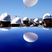 A balloon and hardhat clad employees of the Ocean Honda dealership are reflected on the roof of a new car as workers and guests tour the dealership's new showroom and shop under construction in Soquel, California.<br /> Photo by Shmuel Thaler <br /> shmuel_thaler@yahoo.com www.shmuelthaler.com