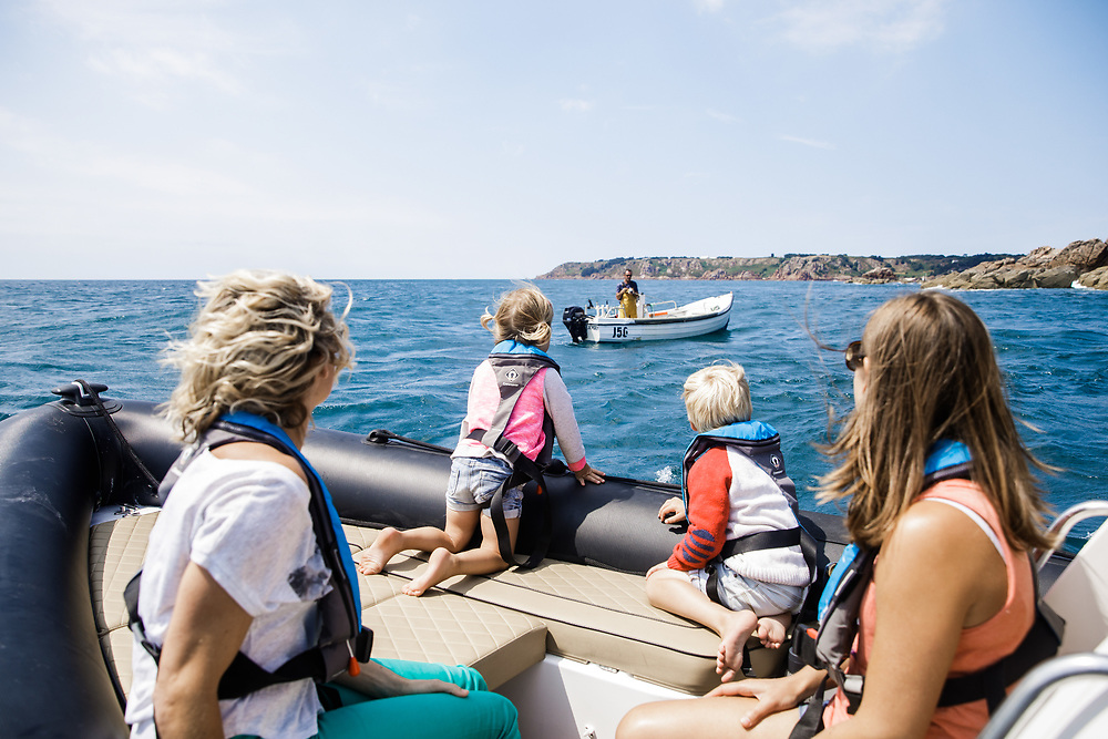 Family on a rib trip watching a man on his boat catching fish off the south coast of Jersey, Channel Islands