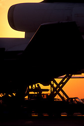 Silhouette of a man doing maintenance on an airliner