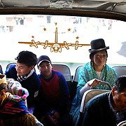 Cholita wrestler Yolanda La Amorosa (right)  travels home on a bus with her daughter after collecting her from school in La Paz, Bolivia. Yolanda is part of the 'Titans of the Ring' wrestling group who perform every  Sunday at El Alto's Multifunctional Centre. Bolivia. The wrestling group includes the fighting Cholitas, a group of Indigenous Female Lucha Libra wrestlers who fight the men as well as each other for just a few dollars appearance money. El Alto, Bolivia, 17th March 2010. Photo Tim Clayton