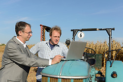 Farmer and businessman checking dates in laptop on cornfield