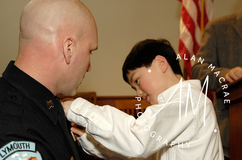 Aidan Temperino pins the Chief's badge on his dad, Plymouth Police Chief Steve Temperino, during ceremonies at the Plymouth Town Hall yesterday afternoon.  (Alan MacRae/for the Citizen)