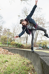 Young man balancing on concrete wall and loosing the balance, Munich, Bavaria, Germany