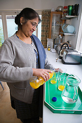 Older woman at home pouring some drinks,