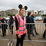 One of several permenently grumpy attendants. Locals queu to get into Dismaland. A thousand locals won a free tickets to an advance look entry to the show. Dismaland, a bemusement park set up by artist Banksy show casing more hand 40 artists. The bemusement park is set in a former lido in Weston Super-Mare. After much secrecy the show opened to a small number of locals from Weston Super-Mare Friday and fully to the public Saturday Aug 22.